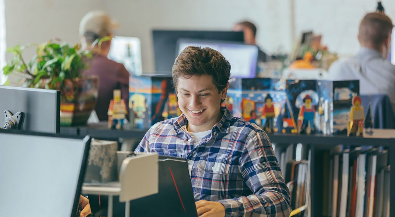 Intern smiling while looking at computer in office setting